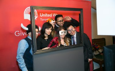 people posing behind a giant frame photo booth