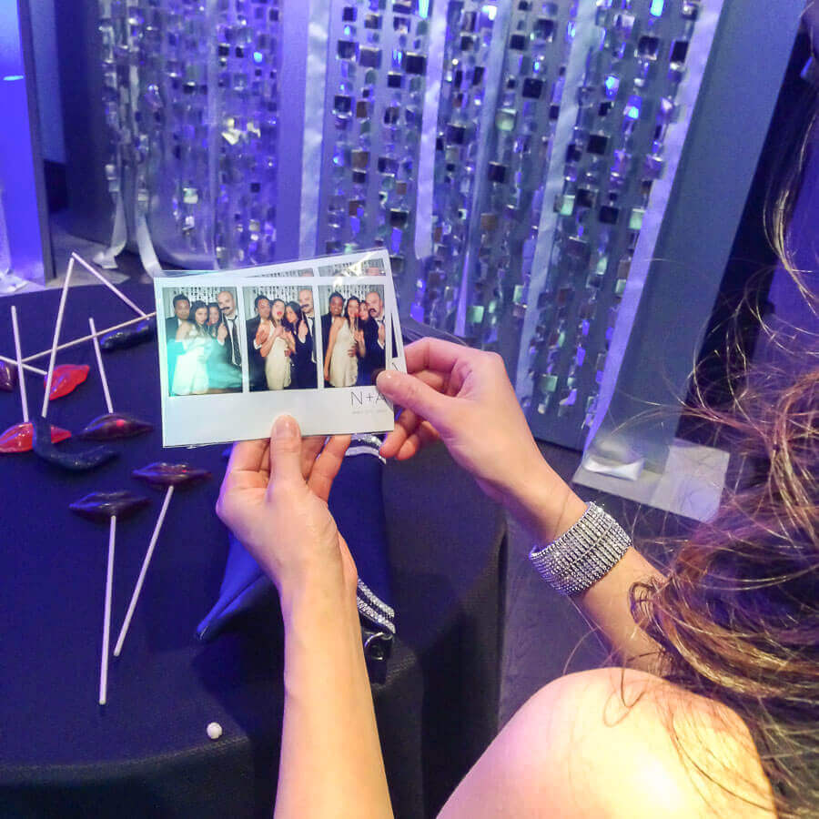 a lovely lady looking at her photo booth prints at a wedding