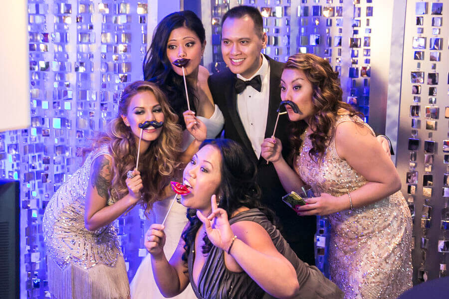 gorgeous guests posing in front of a bespoke glittery backdrop