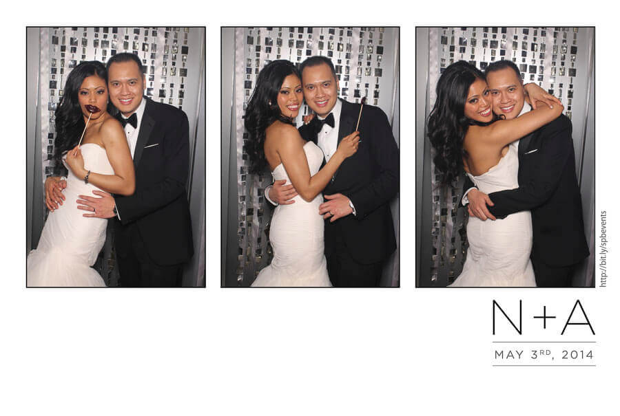 bride and groom at a wedding photo booth with a custom built backdrop