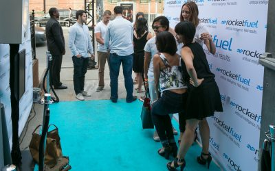 Women posing on the blue carpet for a photo booth opportunity