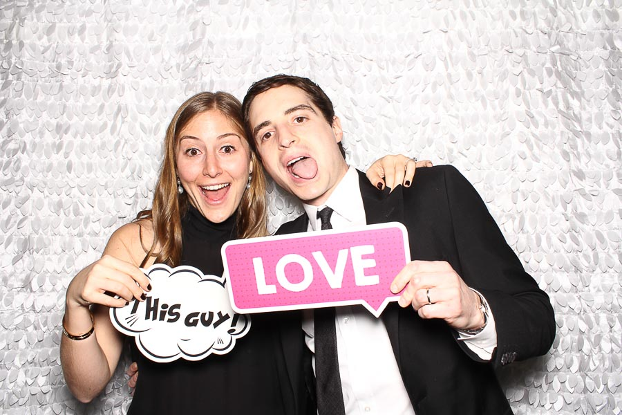 a couple laughing and posing in the photo booth