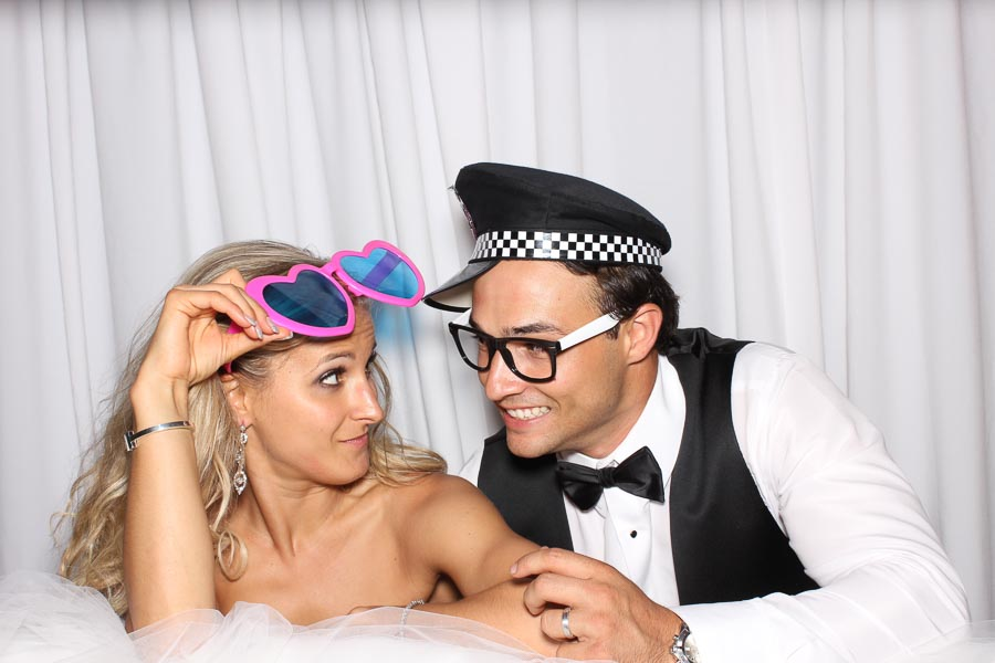 a bride and groom having fun in the photo booth