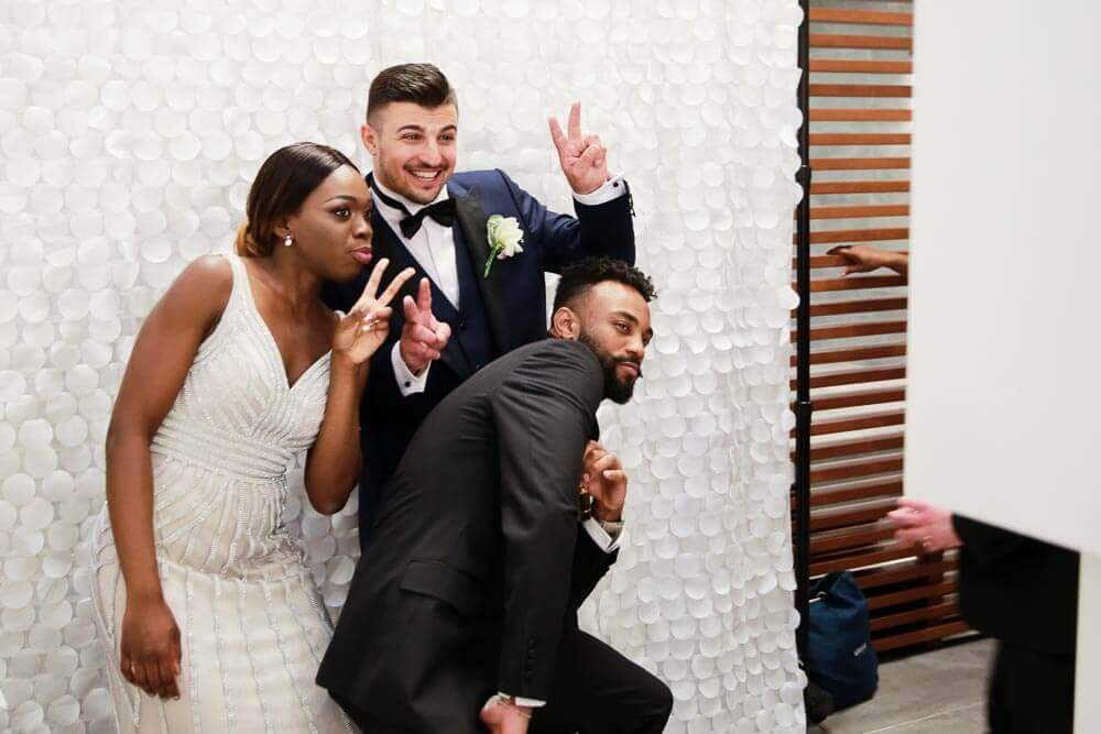 A bride, groom and groomsman posing the wedding photo booth