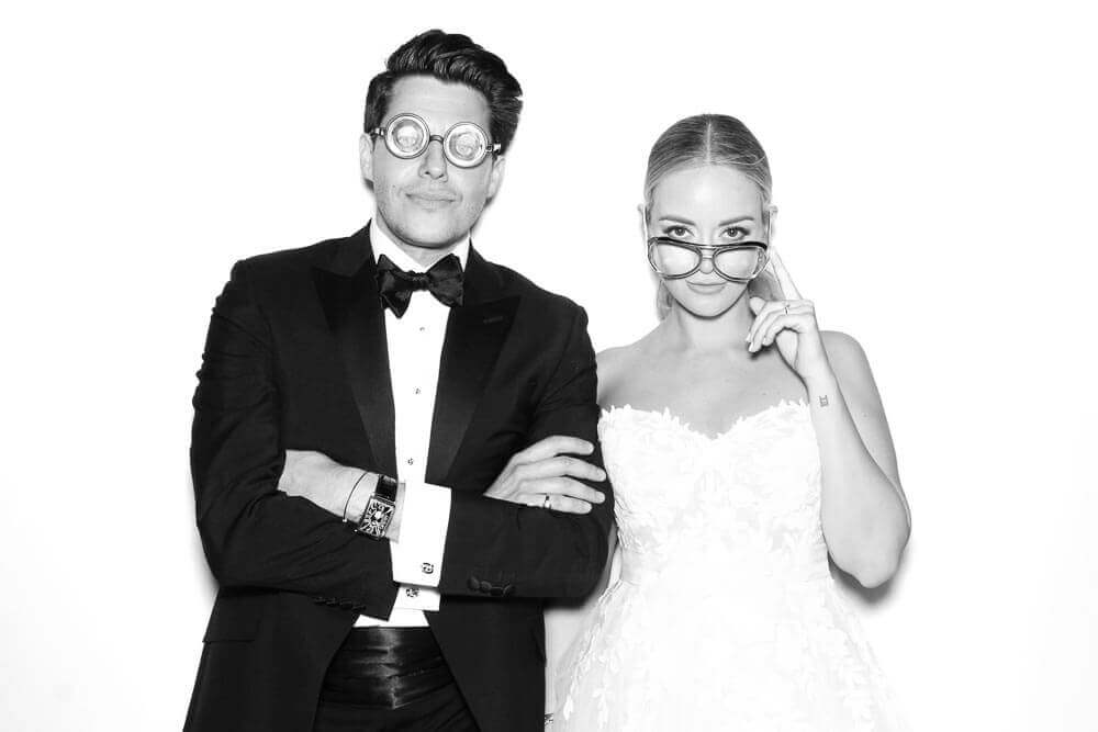 A black and white of a cool bride and groom posing in the wedding photo booth