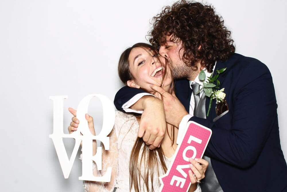 a bride and groom kissing the photo booth