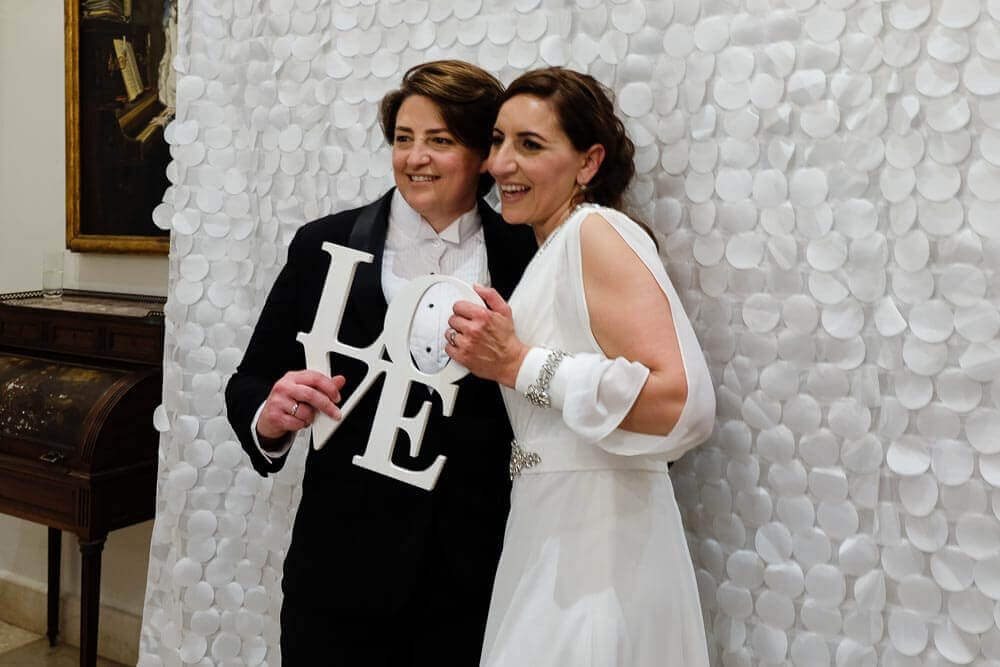 a couple posing with a love sign in the photo booth